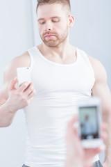 Handsome muscular man taking photo