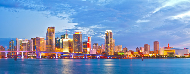 Miami Florida at sunset, cityscape of modern downtown buildings illuminated with reflections in the waters of Biscayne BAy