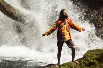 View of happy young man with arms outstretched enjoying in waterfall in the mountains