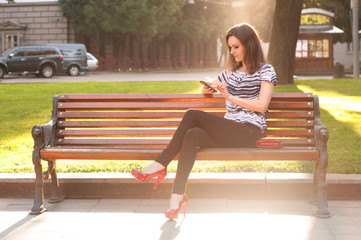 Young beautiful woman sitting on a bench and typing a message on