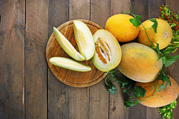 Ripe melons with green leaves on wooden background