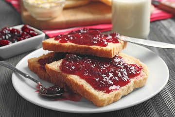 Bread with butter and homemade jam in plate on wooden table, closeup