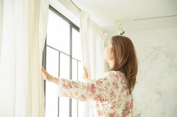 朝の目覚めでカーテンを開ける美しい40代日本人女性