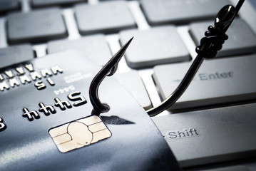 credit card phishing - piles of credit cards with a fish hook on computer keyboard - fototapety na wymiar