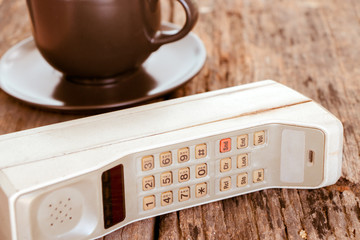 Old mobile phone put on wooden table with cup of coffee, Vintage tone style.