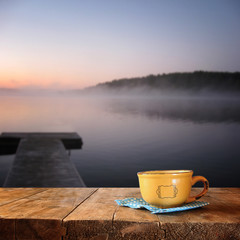 front image of coffee cup over wooden table in front of calm foggy lake view at sunset