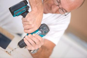 Carpenter using a cordless drill