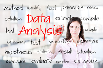 Young business woman writing data analysis concept. Office background.