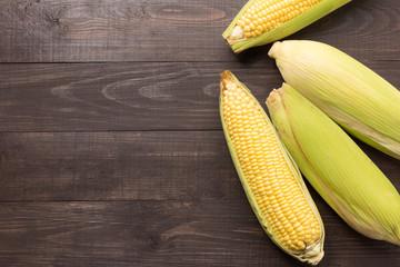 Fresh organic yellow sweet corn on wooden table. Top view