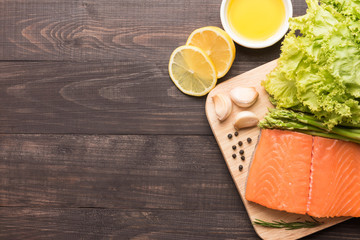 Fresh salmon fillet with spice on wooden background