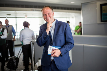 Businessman with passport and boarding pass at the airport