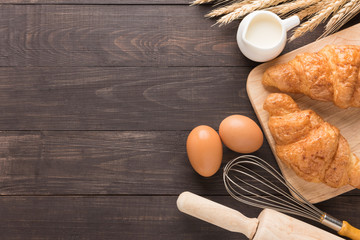 Freshly baked croissants, milk and eggs on wooden background