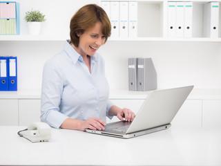 managerin schaut lachend auf ihr notebook