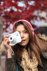 Beautiful Asea young woman holding a camera.