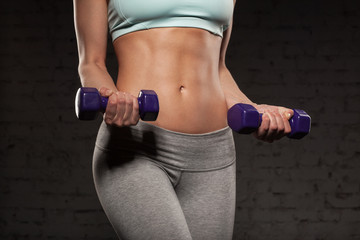 Fitness female woman with muscular body, do her workout with dumbbells, abs, abdominals