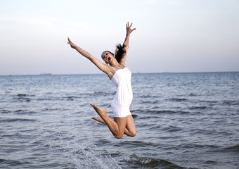 Happy brunette girl jumping over the sea