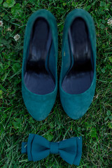 green wedding shoes and a butterfly on the grass