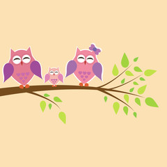 happy family of owls sitting on a tree branch
