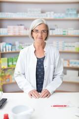 ältere apothekerin vor dem regal mit medikamenten