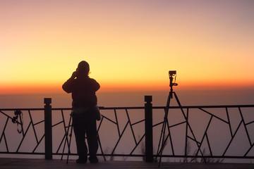 silhouette tourists photograph the sunrise
