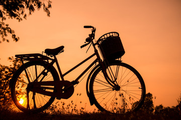 beautiful landscape image with Bicycle silhouette  at sunset