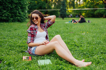 Brown hair girl spending free time, sitting on the grass in the park.
