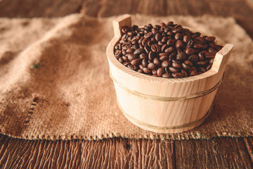 Coffee beans in wooden bowl on wooden background. Selective focu