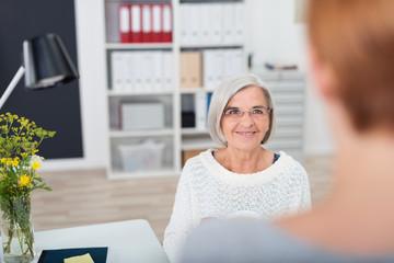 ältere mitarbeiterin unterhält sich mit einer kollegin