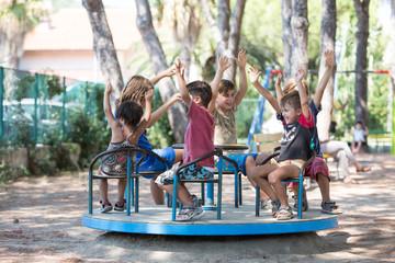 Bambini con le mani alzate che giocano su una giostra Wall mural