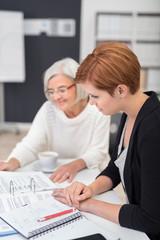 zwei kolleginnen verschiedenen alters in einer besprechung am schreibtisch