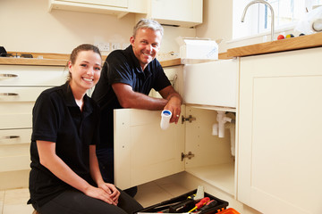 Portrait of male plumber with female apprentice in kitchen
