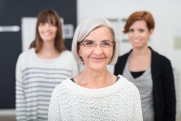 ältere frau im büro mit ihren kolleginnen im hintergrund