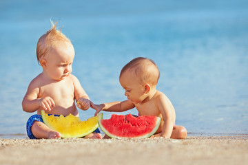 After sea swimming frolic asian baby girl and white boy have a fun and eat fruits on sand beach. Healthy kids food, active lifestyle, water activity and children travel with parents on family vacation
