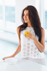 Woman drinking orange juice smiling.