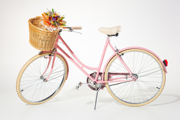 pink vintage bicycle whith flower basket isolated on white backg
