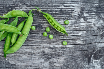 Vintage wooden surface with located pods of green peas