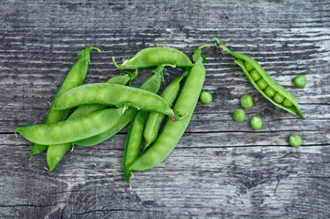 Green pea pods beautifully lie on vintage wooden surfaces
