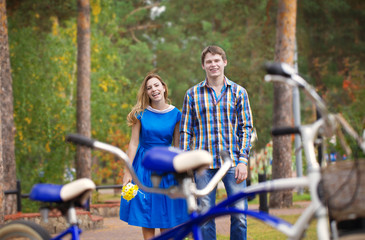Happy young couple in love against the background of a tandem bike