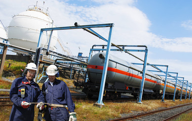 oil and gas workers with train loaded with crude oil and fuel