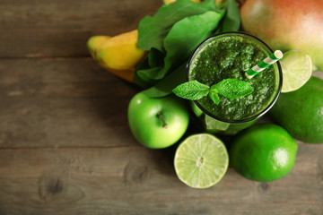 Green healthy juice with fruits and herbs on wooden table close up