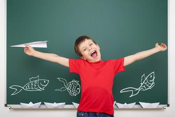 boy drawing fish on school board