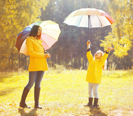 Happy family with umbrellas in sunny autumn rainy day, mother an