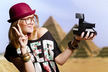 Girl wearing hipster glasses making selfie by polaroid in Egypt