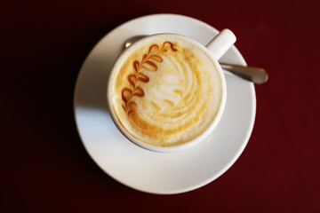 Cup of cappuccino on red napkin, top view