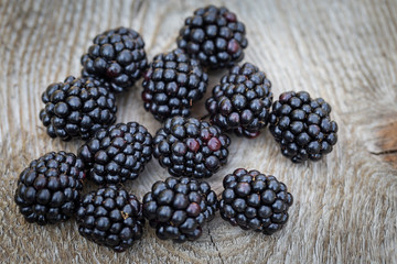 Many blackberries resting on the wooden table