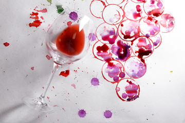 Wineglass of spilled wine with watercolors stains on paper background