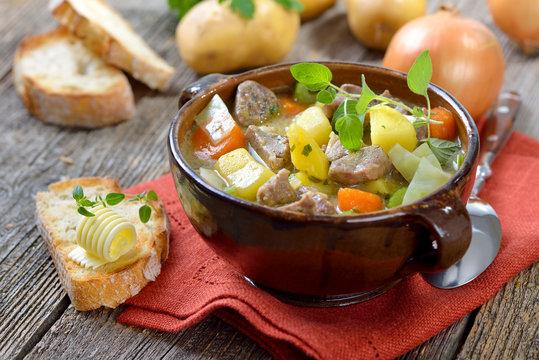 Irish Stew mit Lammfleisch, Kartoffeln und weiterem Gemüse in der Keramikschale serviert