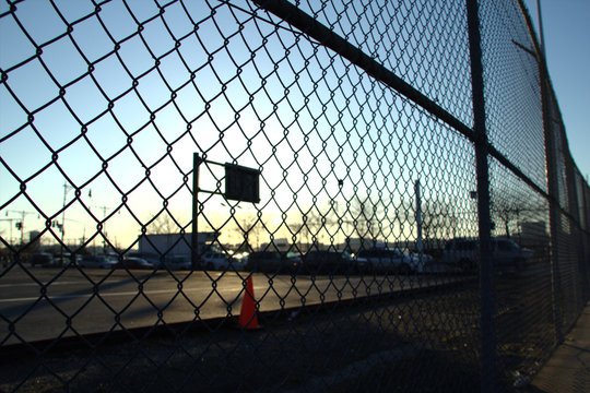 Urban basketball play ground viewed from behind a fence