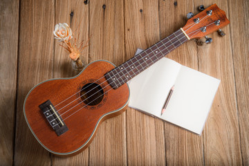 ukulele with notebook on wood background