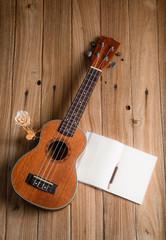 ukulele with notebook on wood background